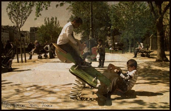 children on playground near seine and notre dame in paris, france