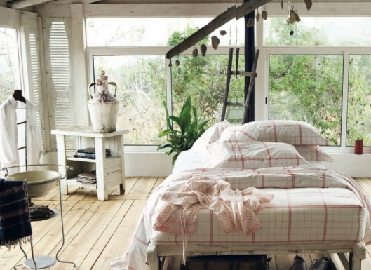 delightful bedroom with wood floors and rustic white and red bedding with view of green outdoors from spring UK catalogue