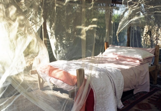 outdoor bed with white and pink bedding draped in mosquito netting from spring Toast UL catalogue