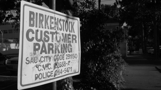 birkenstock customer parking sign in midtown sacramento; black and white widescreen photo