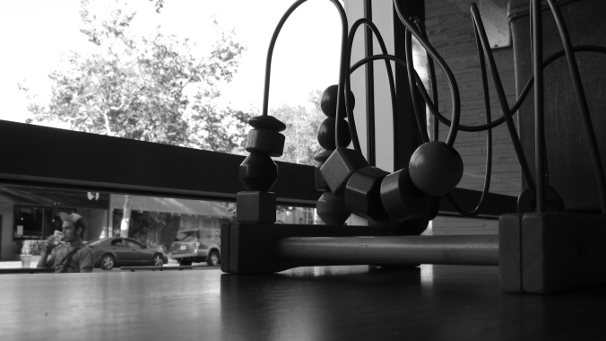black and white photo of wooden block toy in window of coffeeshop