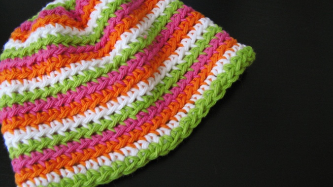 crochet baby hat with lime green, hot pink, bright orange and white stripes