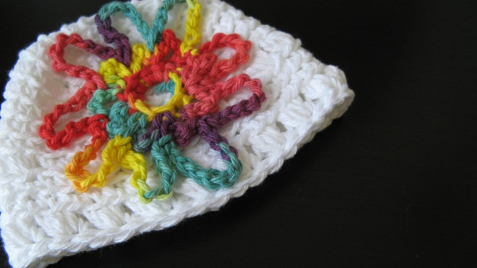 White crochet baby hat with multi-color crochet flower