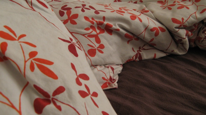 red and orange and white floral pillowcases on brown flannel sheets