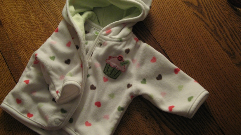 white fleece baby sweatshirt with hearts and a cupcake applique