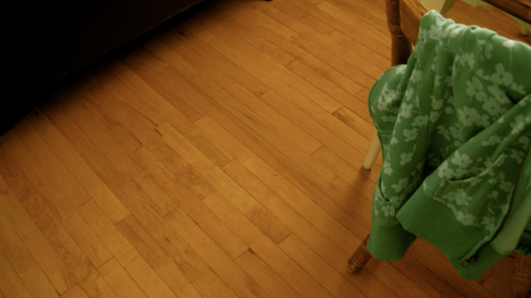 green floral hoodie tossed over back of chair, hardwood floor
