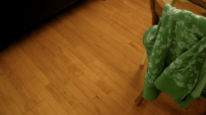 green floral hoodie tossed over back of chair, hardwood floor