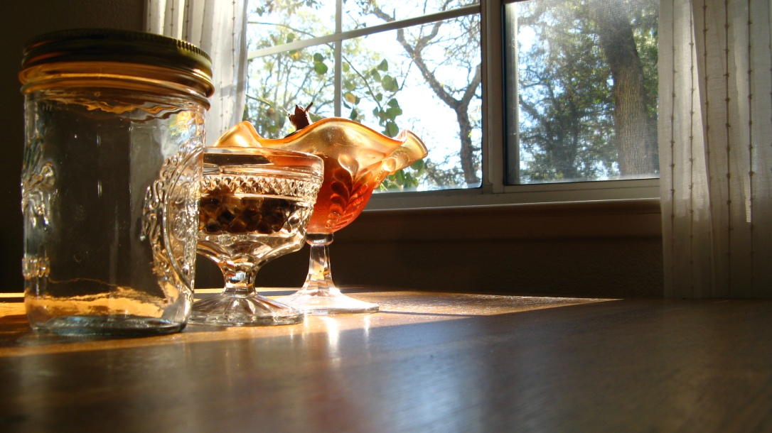 sun shining through window onto wood table with mason jar, crystal ice cream dish, pomegranate and pumpkin seeds - autumn, earth tones, sunshine