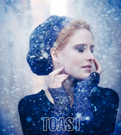 cover of Toast UK's winter book - snow, woman in hat, blue