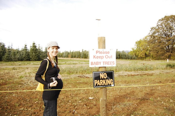 gina (oaxacaborn) at a christmas tree farm at apple hill in camino california next to a 'keep out: baby trees' sign