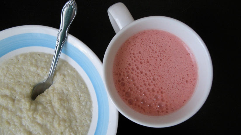 hot quinoa cereal and fresh squeezed pink grapefruit juice - in white dishes and blue dishes on black background