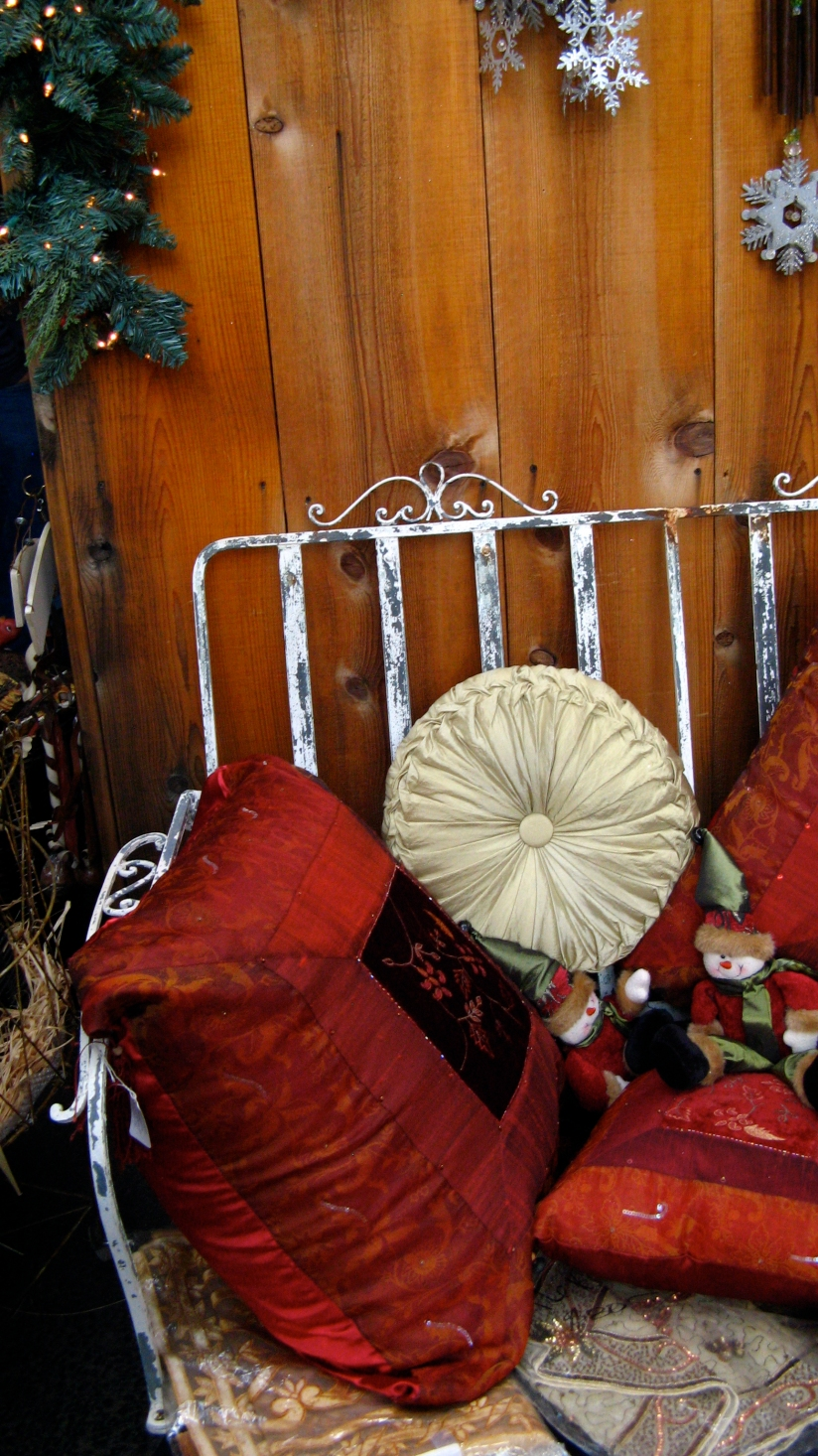 embroidered christmas pillows on patina'd metal bench against wooden wall at apple hill in camino california