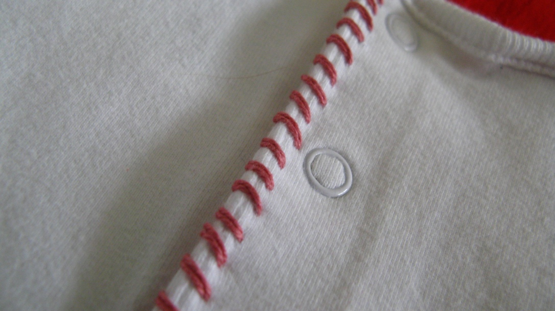 embroidered pink thread on back snaps of a white baby onesie