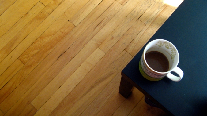 coffee mug on a black Ikea coffee table in a hardwood floor living room