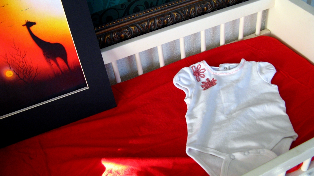 white changing table with red changing pad cover, white embroidered onesie, and orange-red giraffe safari art