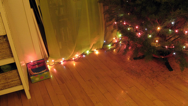 on the first day of christmas - image of christmas light string around base of christmas tree, glowing against wood floors