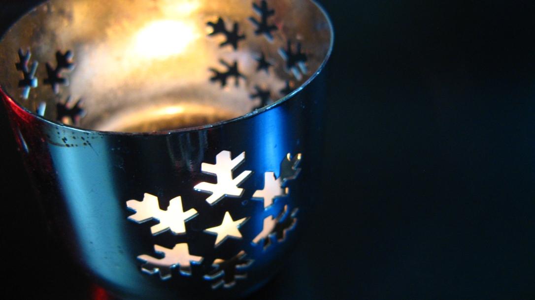 silver metal votive holder with diecut snoflake design - lit with tea light on black background