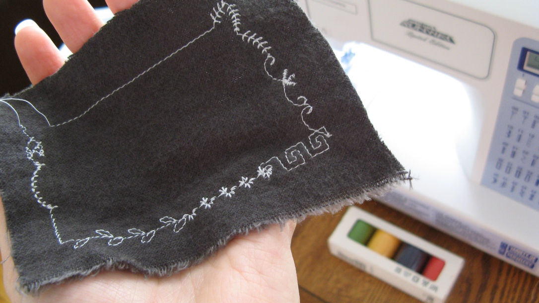 sample decorative stitches in white thread on grey flannel