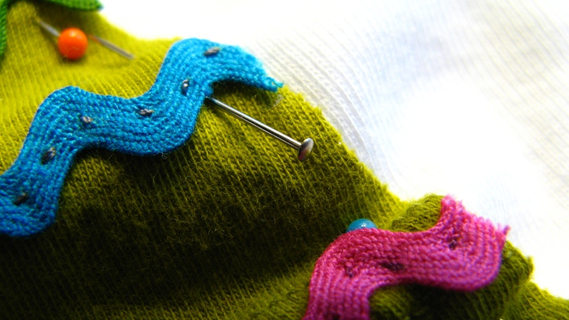 closeup macro shot of turquoise and pink vintage rickrack pinned to a green and white background