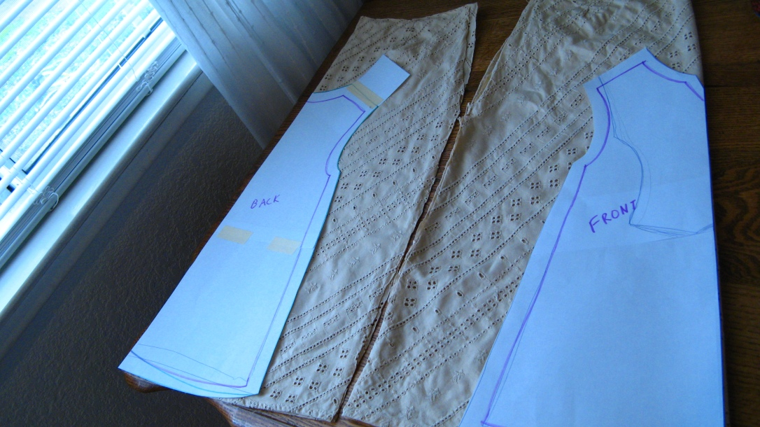 homemade baby girl dress pattern laid out on old skirt fabric