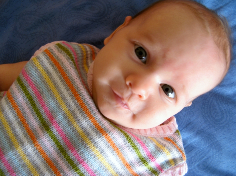 Two month old baby girl wearing knit striped sleeveless sweater