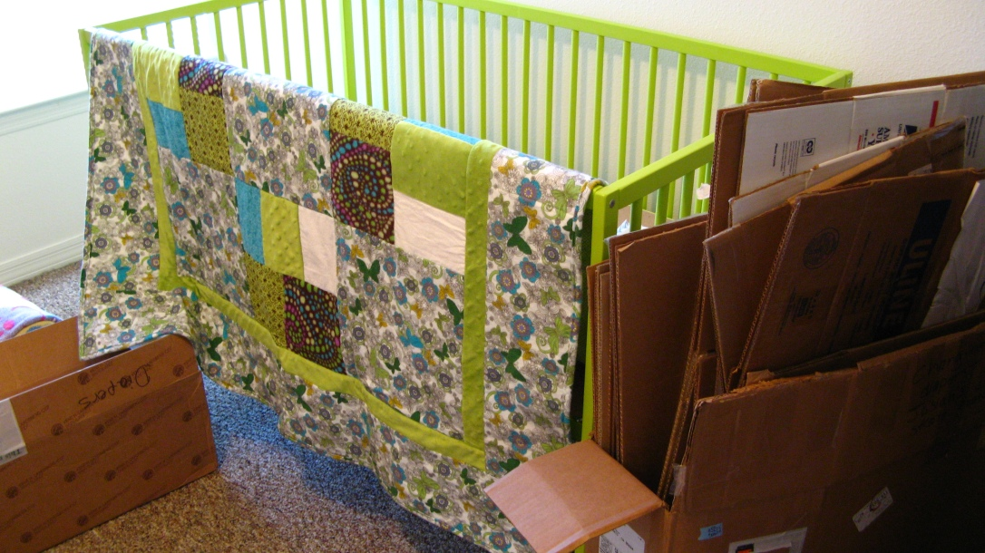 lime green IKEA Somnat crib - with handmade quilt and stack of flattened moving boxes nearby