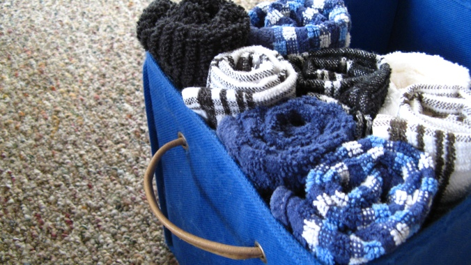 rolled up blue, white and black kitchen towels in blue canvas storage container