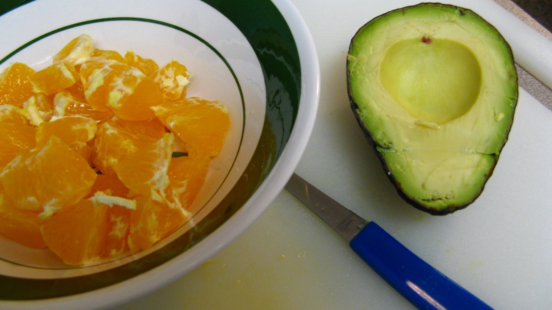 pieces of navel orange and half avocado on cutting board with paring knife