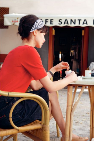 image via early spring '11 toast uk catalogue - woman in red top and black skirt at cafe table with coffee