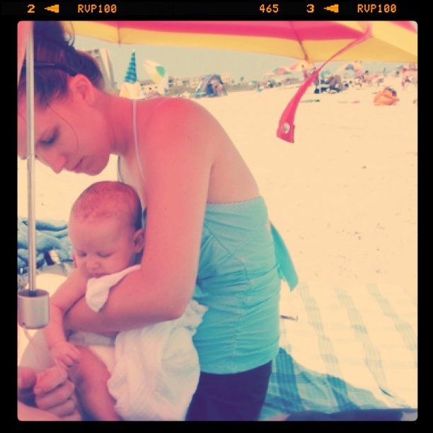 Gina and Aveline under umbrella at Cocoa Beach - baby's first trip to the Atlantic Ocean