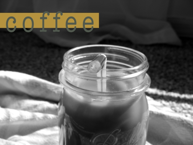 black and white photo of iced coffee in mason jar with straw