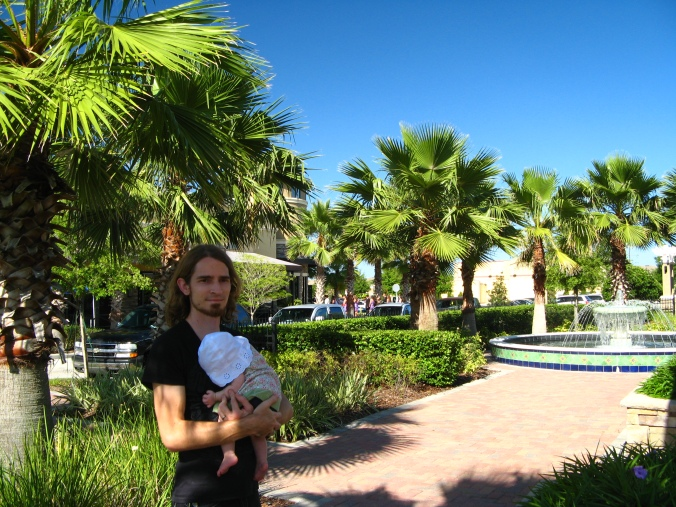 26pm holding daughter baby aveline near palm trees - daddy's shirt from o'neill, baby's clothes from the childrens place