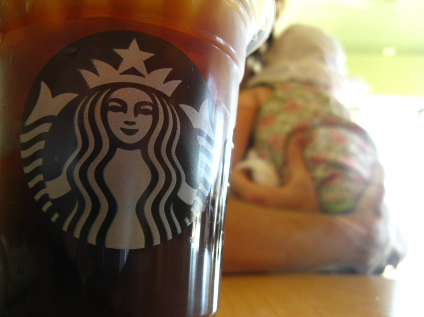 starbucks iced americano with baby in background