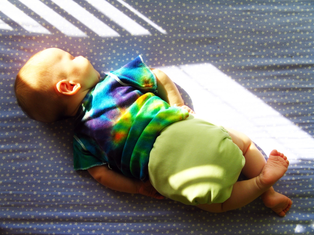 sleeping baby in tie-dyed shirt and yellow cloth diaper sleeping on blue and white star patterned crib sheet in the sunshine