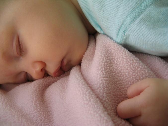 baby fast asleep on pink fleece blanket