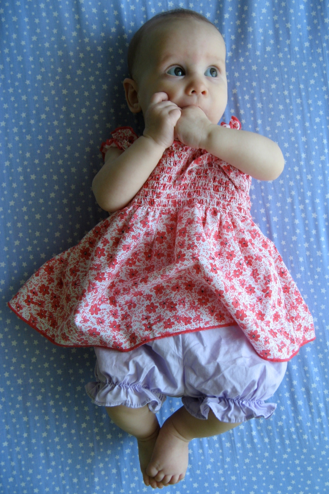 my beautiful baby girl wearing a pink calico dress and lavender bloomers, laying on periwinkle fabric
