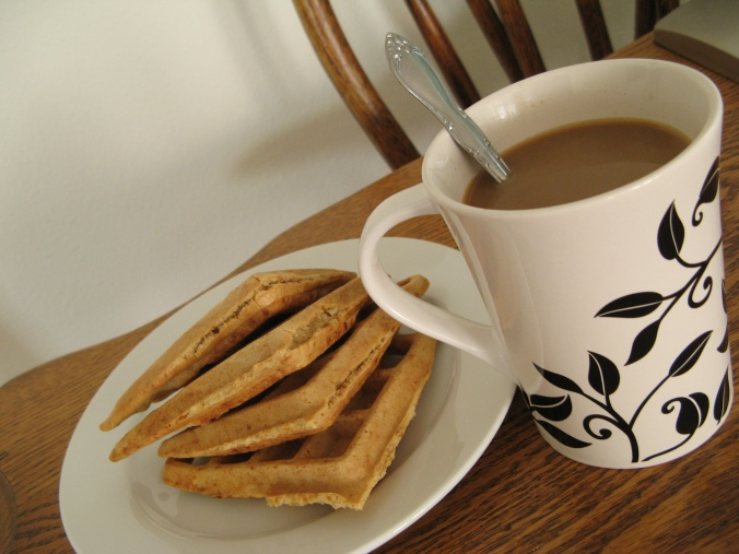 gluten-free waffles on white ceramic plate, coffee in white and black mug, on wooden table
