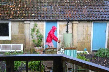oaxacaborn outdoor pinterest board - cottage with blue doors, gardener in pink raincoat - via mytinyplot.co.uk