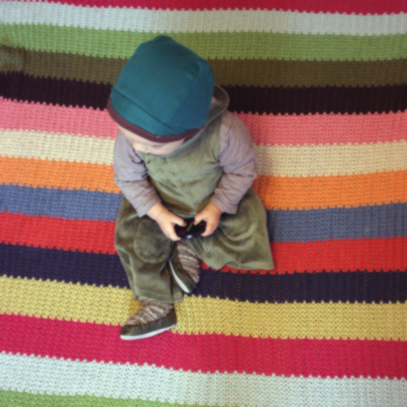 Artsy Ants - Sylvia - Photograph of  Child on Striped Blanket