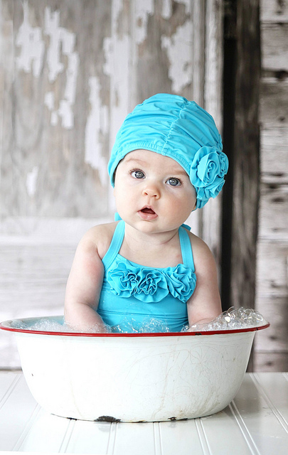 Baby in White and Red Enamel Washbasin Wearing Turquoise Ruffled SwimSuit - via cBaase