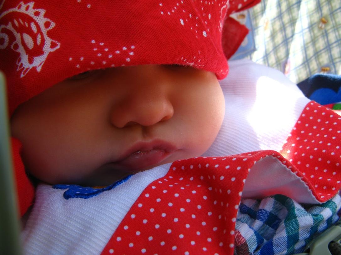 Aveline wearing red bandana and gingham/polka dot dress