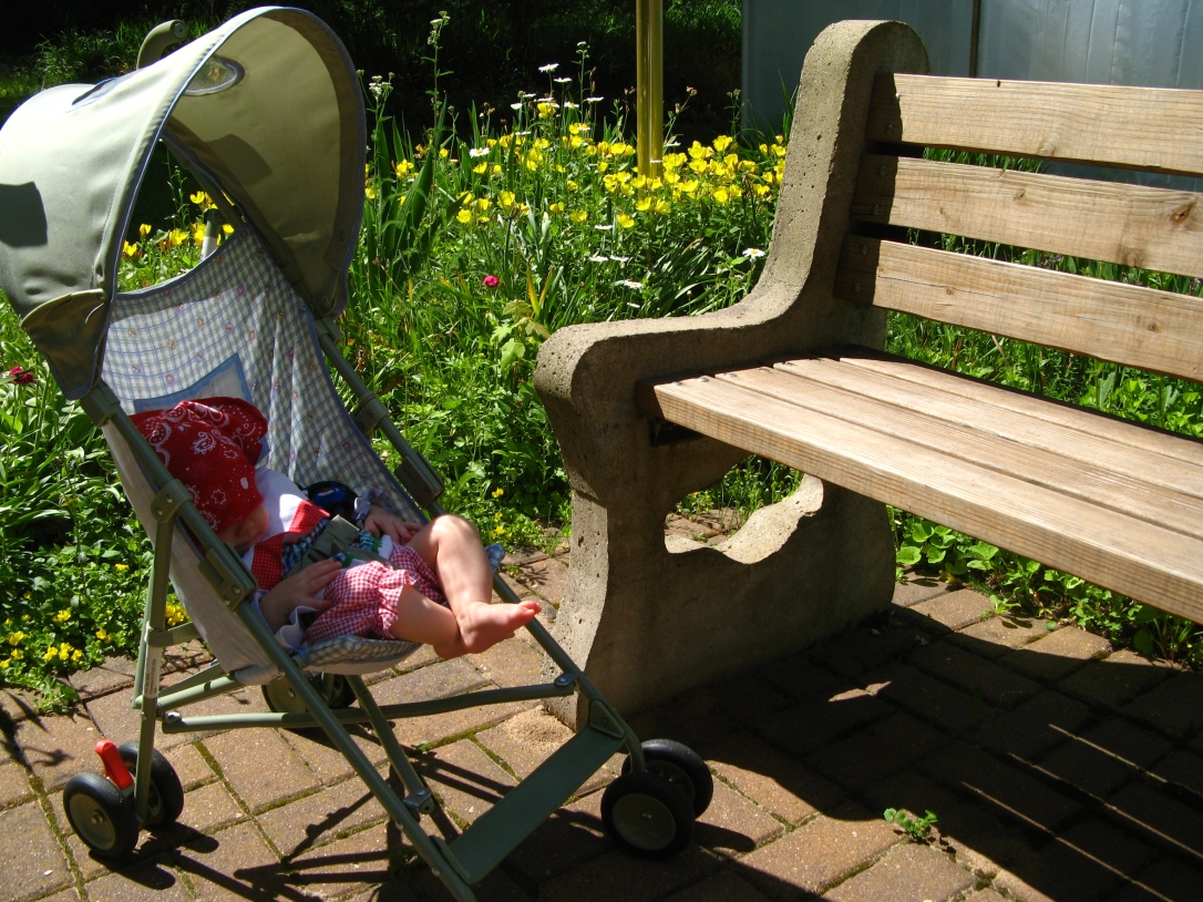 Aveline in small stroller next to garden bench