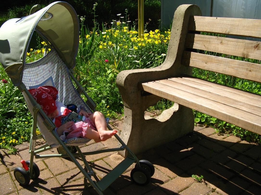 Aveline in small stroller next to garden bench