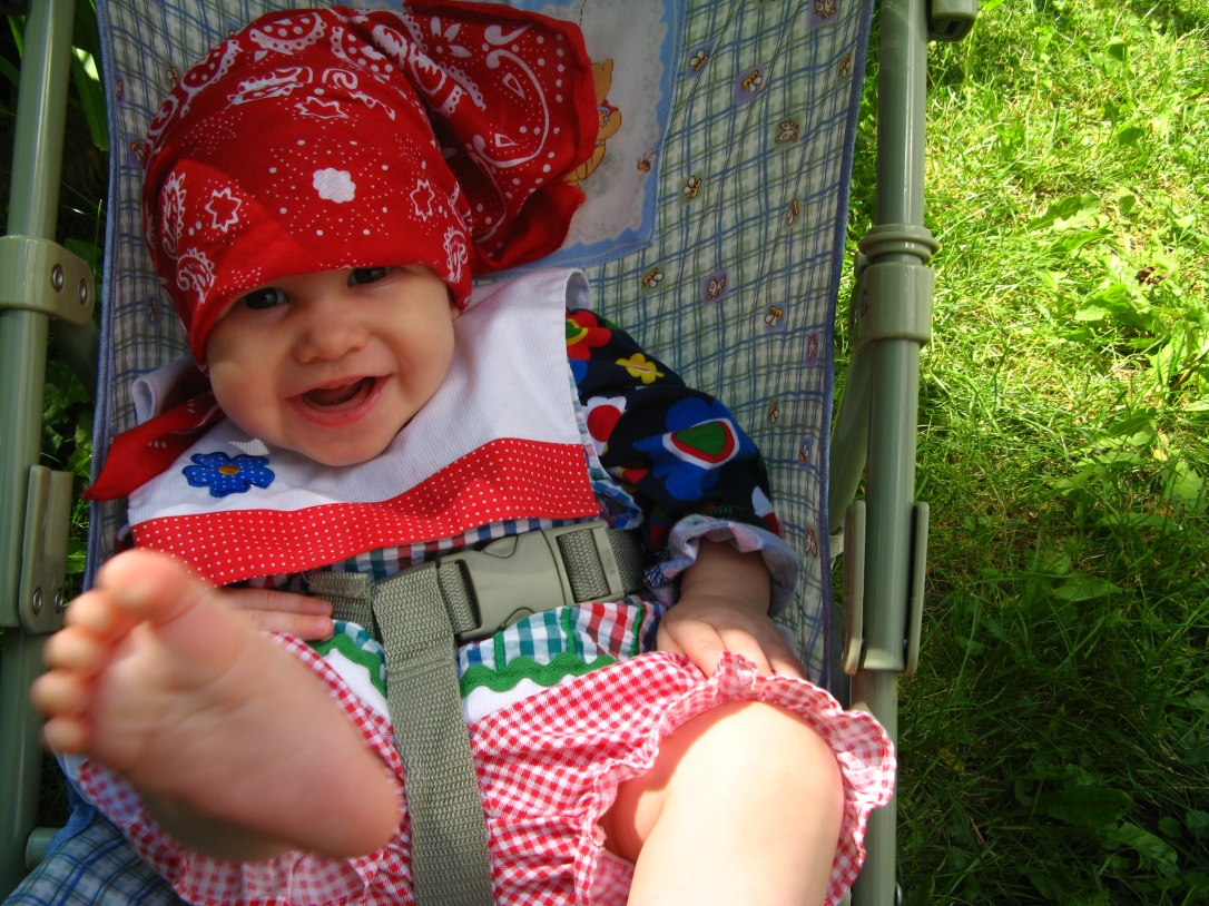 Aveline wearing red bandana and gingham dress, kicking bare foot into camera