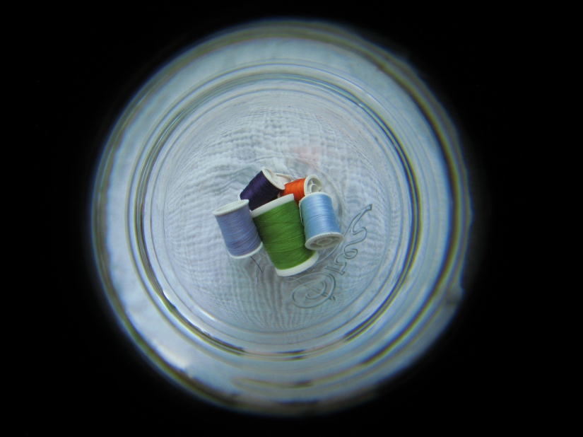 Spools of thread inside a glass mason jar, photographed with fish-eye lens