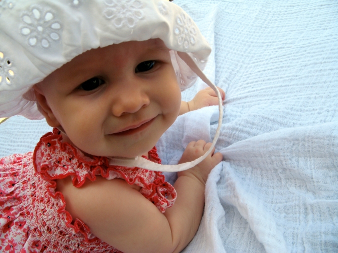 Baby Aveline in pink calico dress and white eyelet lace sunhat