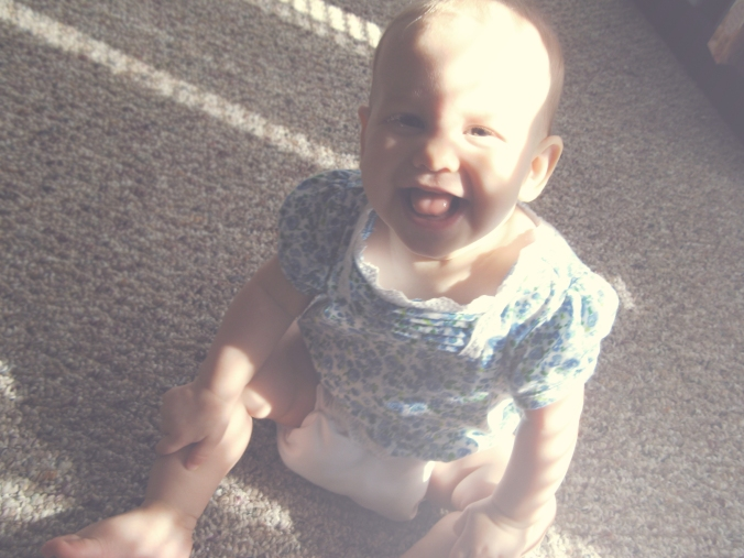 Baby sitting on floor, laughing, in filtered desaturated summer sunlight