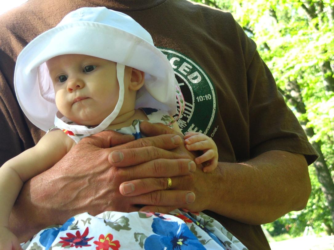Aveline in white sunhat, held by Grandpa