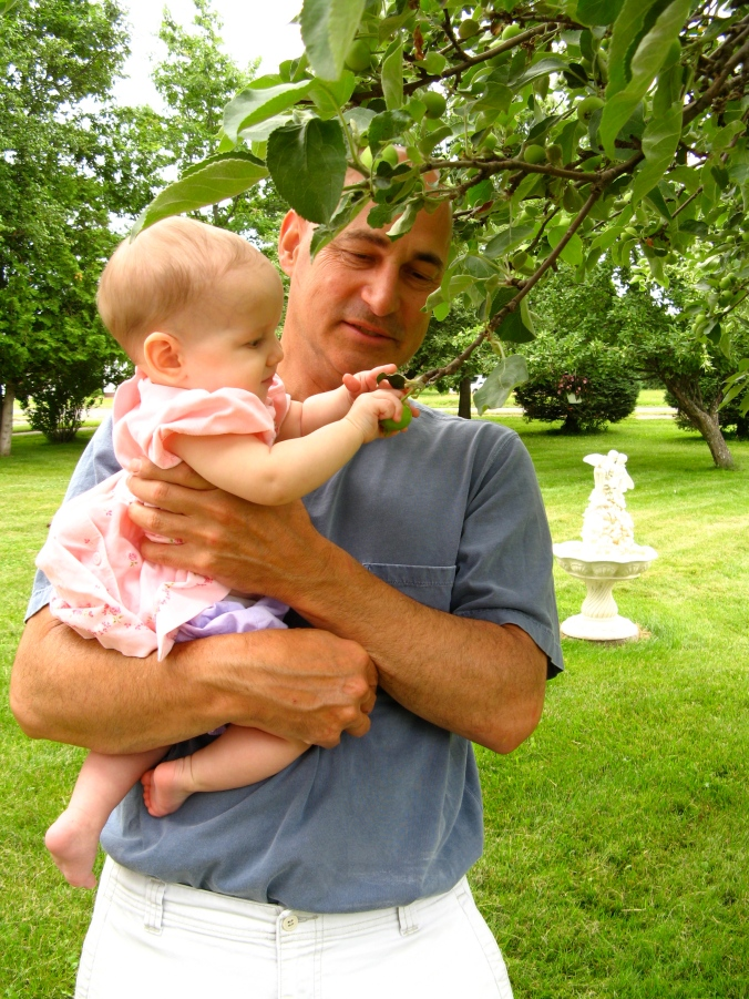 Great Uncle Chet holding Aveline, letting her pick a young apple off a tree in Caspian Michigan