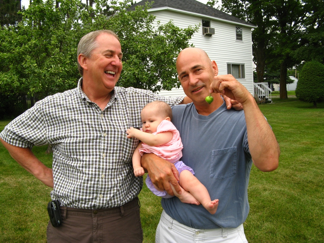 "My Dad (Grandpa ""Bumpa"" Jim) and his brother Chet with Aveline, holding a small Michigan apple Aveline had just picked off the tree"